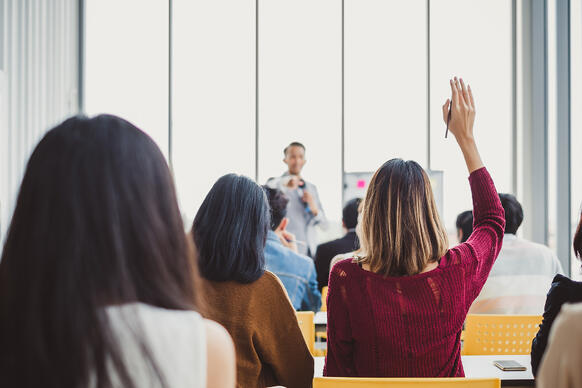Woman raising her hand in a classroom of business professionals