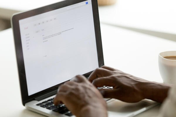 African-American man typing email on silver laptop